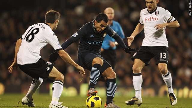 Manchester City's Carlos Tevez evades the attentions of Fulham's Danny Murphy and Aaron Hughes at Craven Cottage.