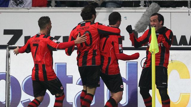 Eintracht Frankfurt players run to scorer Theofanis Gekas after his later winner against Borussia Dortmund.