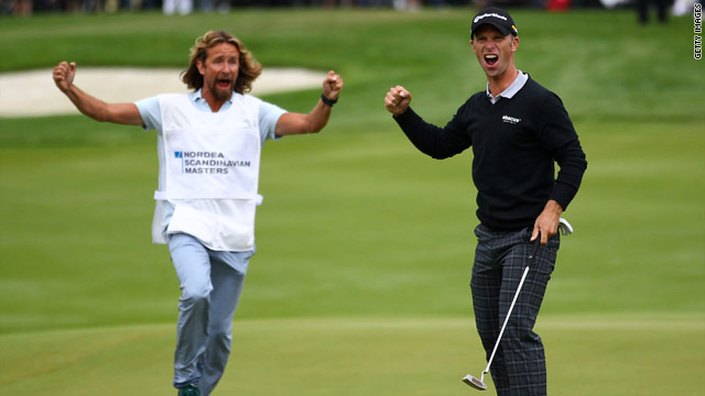 Richard S. Johnson and his stand-in caddy Anders Timmell celebrate after the Swede sinks his decisive title putt.