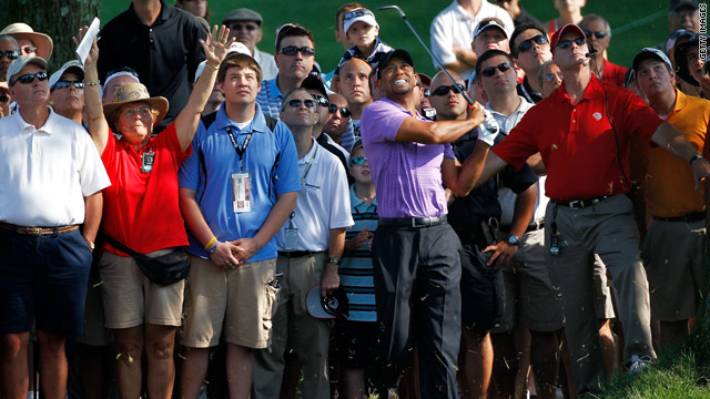 Tiger Woods watches his shot from the rough on the 10th hole in front of a gallery of fans during the second round.