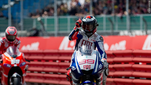 Lorenzo signals victory as he takes the checkered flag at Silverstone.