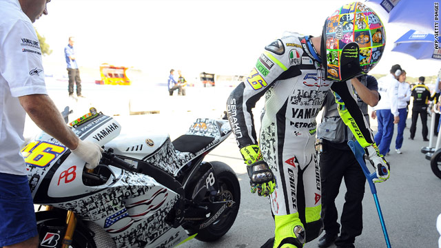 Italian motorcycling star Valentino Rossi leaves the track at Laguna Seca with the help of a walking stick.