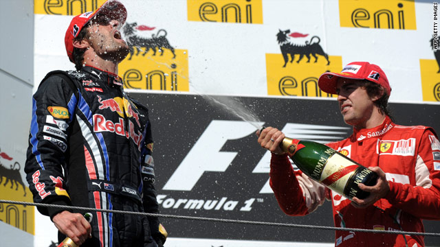 Hungary runner-up Fernando Alonso showers new F1 drivers' leader Mark Webber with champagne after his victory.