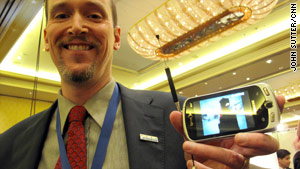 John Godfrey, of Samsung, shows off a demo mobile phone that can pick up and play local TV.