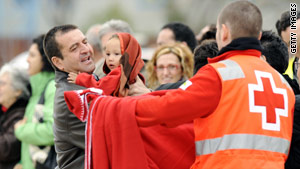 A Red Cross member at a Madrid airport January 12 hands blankets to arriving Spanish and Haitian earthquake survivors.