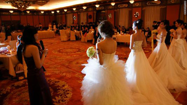 Brides to be? Young women selected for their eligibility pose in wedding gowns at an event for millionaire bachelors.