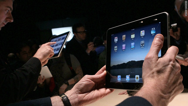 Reporters try out the iPad -- for sale on April 3 -- at Apple's January unveiling.