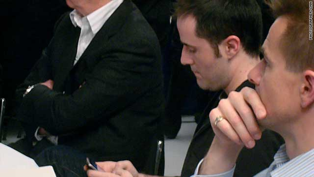 Twitter co-founder Evan Williams finds time to use his own service during the social media discussion at Davos.