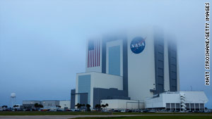 Poor weather conditions at Kennedy Space Center scrapped Discovery's landing plans. NASA will try again Tuesday.