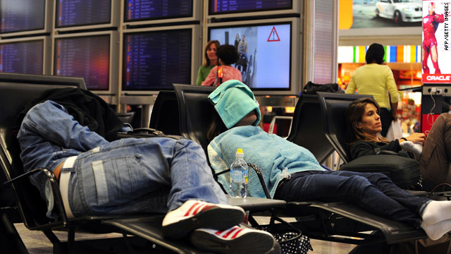 Air travelers in Frankfurt, Germany, stretch out Friday while they wait for service to resume.