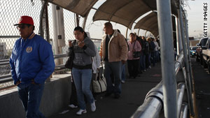 People wait in line at the border of the United States and Mexico.