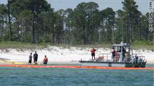 A containment boom is laid at Pensacola beach to protect the shore from the approaching oil.