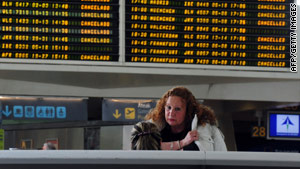 A passenger stands in front of a board showing canceled flights Saturday in Bilbao, Spain.