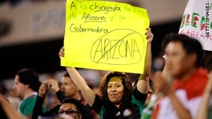 A fan hoists a protest sign during an international baseball tournament game Friday in New Jersey.