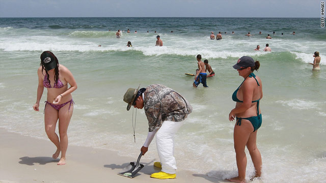 A worker removes small globs of oil that have washed up on Pensacola Beach, Florida.