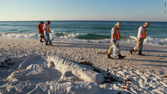Workers pick up oil residue Tuesday that has washed up on Pensacola Beach, Florida.