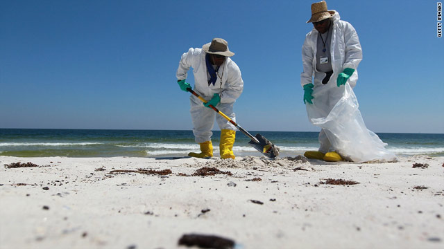 Workers clean up patches of oil Tuesday on the beach at Bon Secour National Wildlife Refuge in Gulf Shores, Alabama.