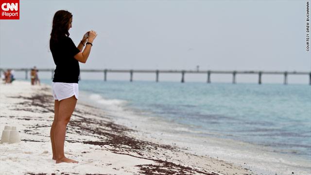 A beachgoer takes photos where oil has come ashore on Okaloosa Island in Florida.