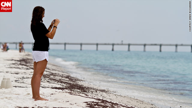 A beachgoer takes photos where oil has come ashore on Okaloosa Island in Florida.