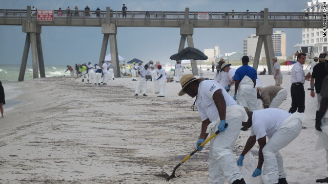 Workers clean a stretch of beach affected by oil in Pensacola Beach, Florida, on Wednesday.