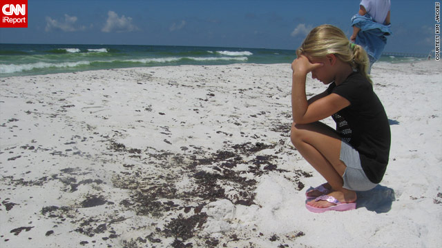A girl watches with disbelief as oil comes ashore this week on Pensacola Beach, Florida.