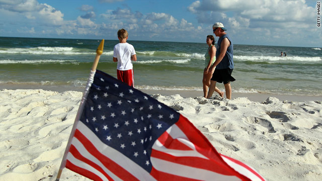 Visitors walk on the beach in Gulf Shores, Alabama, on July Fourth.