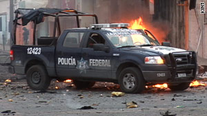 A police truck is parked in front of the remains of a car that exploded in a bombing in Juarez, Mexico, earlier this month.