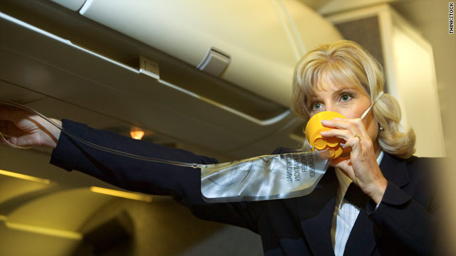 A flight attendant demonstrates safety procedures before takeoff. The job was once considered glamorous.