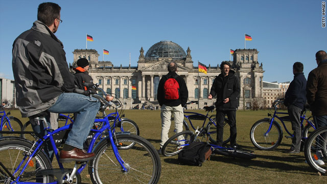 A group of tourists takes in the Reichstag on a cloudless day last spring. Bicycle tours are popular in Berlin.
