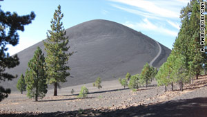 The Cinder Cone emerges after a hike through a forest. The line on its right side is the trail to the top.