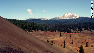 The climb to the top includes views of mountain peaks and the colorful Painted Dunes.