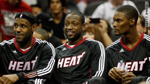 LeBron James, Dwyane Wade and Chris Bosh, from left, sit on the bench during a pre-season game.