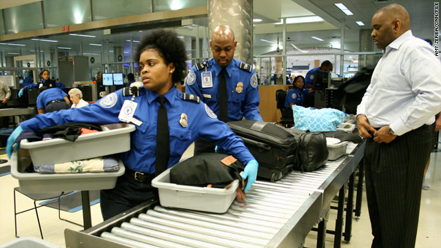 TSA officers check bags at Hartsfield-Jackson International Airport in Atlanta, Georgia. Some airports use private security.