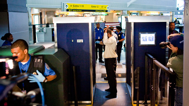 An air traveler undergoes a body scan at an airport.
