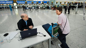 Alain de Botton chats with a passenger at his desk in Terminal 5 of Heathrow Airport.