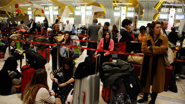 Travelers wait at Madrid's Bajaras airport on December 3. Air traffic controllers called in sick en masse across Spain Saturday.