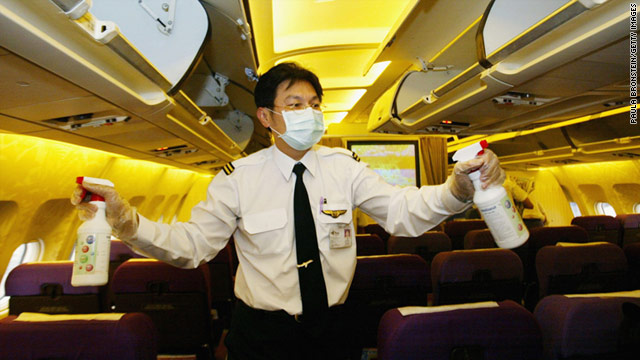 A flight attendant sprays disinfectant onboard a Thai Airlines flight to Chiang Mai from Bangkok.