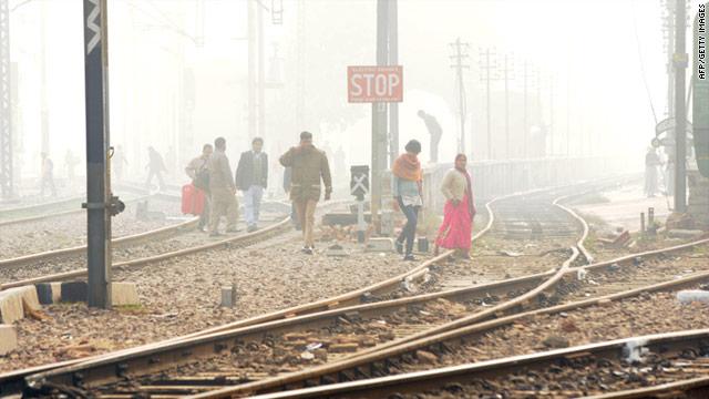 People make thier way through dense fog on an Indian  railway line New Delhi on Sunday.