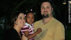 Missy and Mike Wilson hold newly adopted Tia, who survived the earthquake but is still in Haiti.