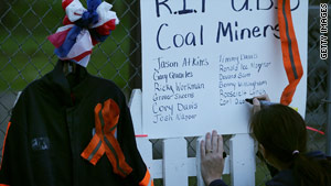 Mickie Green writes the names of 29 fallen coal miners on a small memorial April 10 in Whitesville, West Virginia.