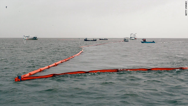 Workers deploy a boom in Drum Bay, Louisiana, on Sunday in an effort to control the oil spill in the Gulf of Mexico.