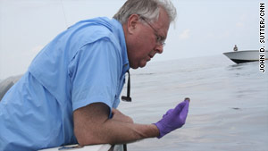 Ed Overton takes a simple oil sample about 10 miles off the coast of Louisiana.