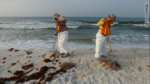 Workers clear Pensacola Beach in Florida as oil residue washes up on shore Monday.