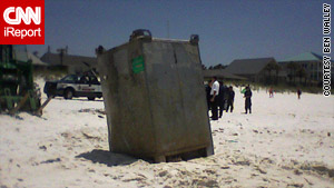 A larger container with BP markings washes ashore Saturday on a part of a beach in Panama City, Florida.