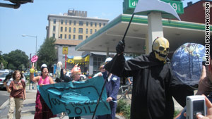 "Protesters, including a ""Grim Reaper"" who poured syrup over a globe to symbolize oil ruin, were out Saturday."