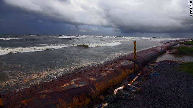 Heavy seas pushed by Hurricane Alex began pounding oil booms lining the shore at Port Fourchon, Louisiana.