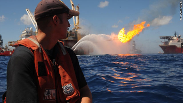 A Coast Guard petty officer watches oil and gas being flared off the Q4000 vessel as crews take advantage of good weather.