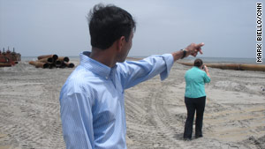 Louisiana Gov. Bobby Jindal points to under-construction sand berms that he says are keeping oil off the shore.