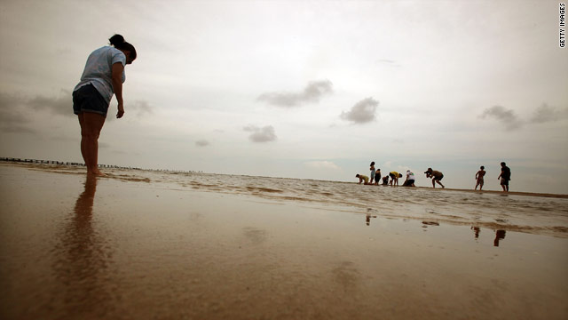 A family plays on a reopened beach July 16 in Waveland, Mississippi.
