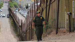 A US Border Patrol officer keeps watch over the border fence that divides the U.S. from Mexico in the town of Nogales, Arizona.